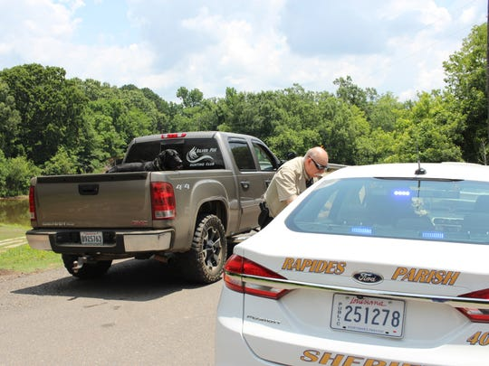 A pickup truck passes Rapides Parish Sheriff's deputies as a search continues Tuesday for three Monroe armed robbery suspects who fled into the Rigolette area.