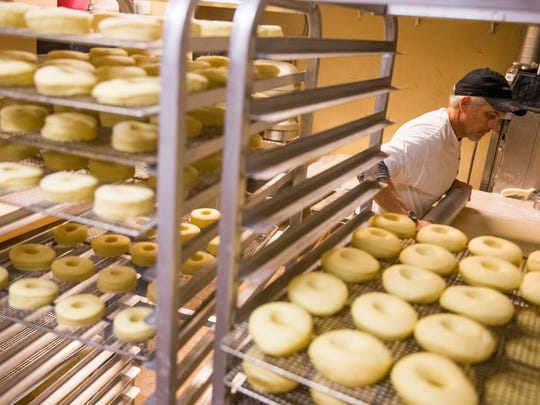 Surrounded by trays of fluffy yeast doughnuts, Dave Resch continues to knead, flatten and form hundreds of the breakfast treats in preparation for the morning rush Tuesday, May 22, 2018, at Trackside Donuts & Cafe in Bonita Springs. Resch, baker Martin Estremera and co-owner Susie Alansky begin preparation at 9 p.m. and work through the early morning hours to satisfy their customers' need for the doughy treats.