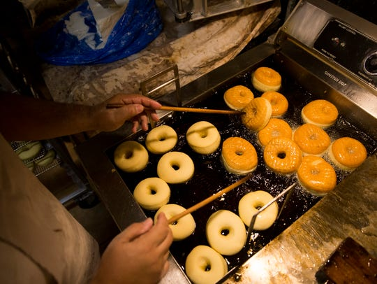 Baker Martin Estremera fries a batch of yeast donuts