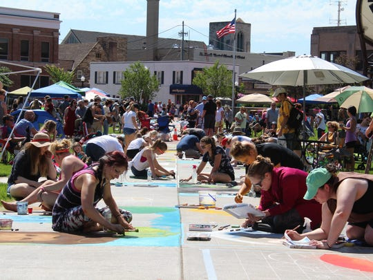 Crowds watch as artists take part in Chalkfest in downtown Wausau on Saturday.