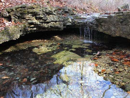 A small waterfall trickling into a crystal clear pool