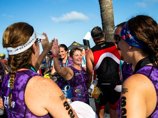 Lisa Briggs, center, high fives her teammates after finishing the 32nd annual Naples Fitness Challenge Triathlon at the Naples Beach Hotel and Golf Club on Sunday, June 3, 2018. The sprint competition event is known for it's 3.1-mile run, 9.3-mile bike and 1/4-mile Gulf of Mexico swim reverse format.