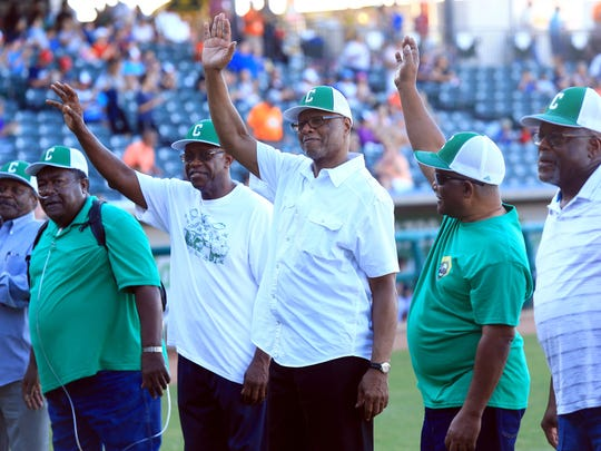 Members of the 1965 Coles High School baseball team wave as they take the field Thursday June 04, 2015 at Whataburger Field. The Hooks honored the 1965 Coles High School state championship baseball team.