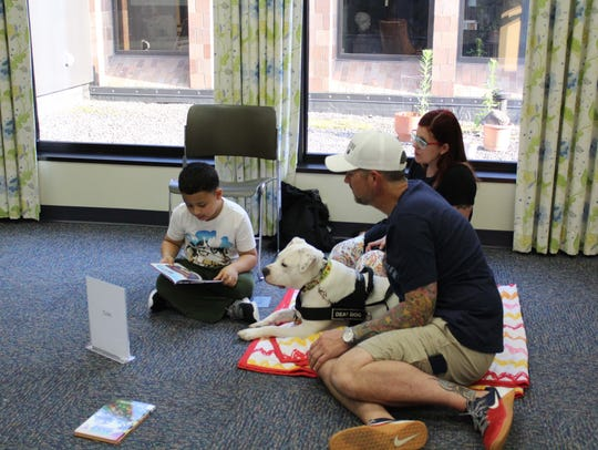 Jeremiah Jimenez, 6, reads to Cole as Cole's handlers,