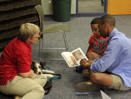 Darwin Cooper helps his son Jayden, 6, read to therapy