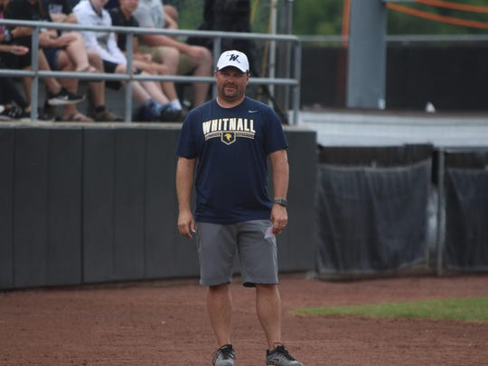 Whitnall head coach Tom Hickman coaches at third base