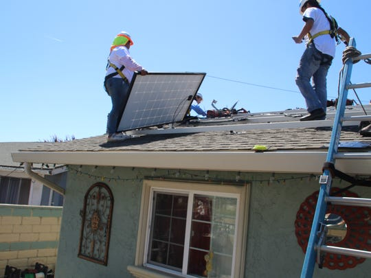 Adrian Aguirre (left) and Cesar Serrano, both interns with GRID Alternatives Central Coast, install the solar panel set on a Salinas home Monday. It's the 1,000th Central Coast home to receive a free solar panel set and installation.