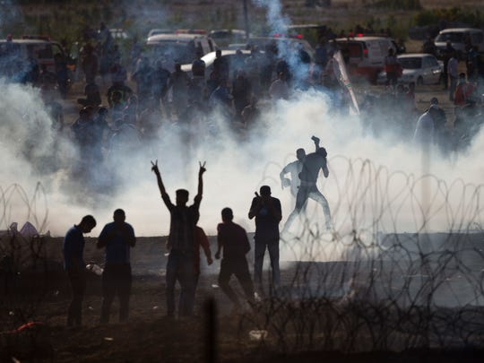 Palestinians protesters run from tear gas fired by Israeli troops in Israel Gaza border, Friday, June 8, 2018.