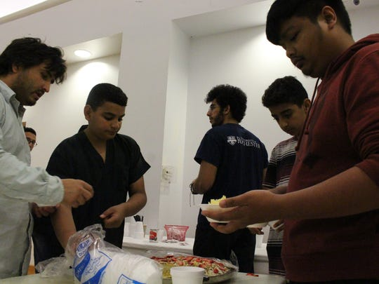 A group of community members help themselves to dessert