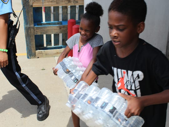 Eight-year-old Terrell McClinton and his sister, Keeniya James, 5, carry water out of a fire station on E. Michigan Avenue in Battle Creek for their family.