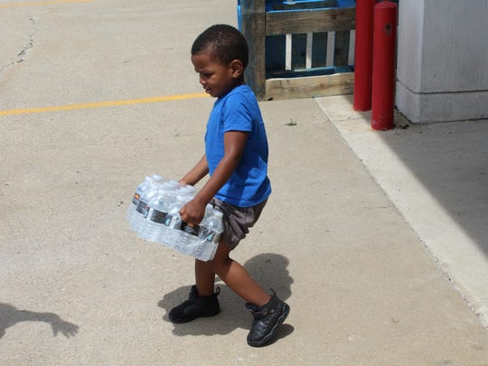 LaQuan James, 3, carries water out of a fire station in Battle Creek for his family.