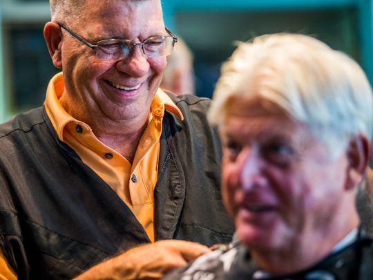 Bob Johns laughs as he works on customer's hair at the Naples Park Barber Shop on Friday, June 15, 2018. T