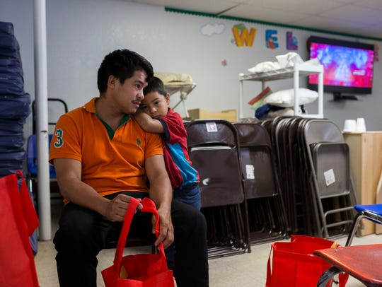 Genin Rodas, 29, and son Edison, 5, from Sabá, Honduras, embrace each other as they wait for a family member to buy them a bus ticket after being released by U.S. Immigration officials at the Catholic Charities Rio Grande Valley refugee center in McAllen, Texas. (Photo: Casey Jackson, Corpus Christi Caller-Times)