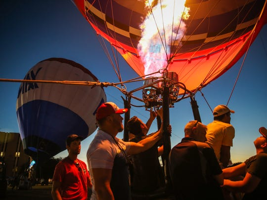 People hang onto the basket of a hot air balloon during Balloonfest Glow Friday, June 15, 2018, at John Glenn Middle School football field.