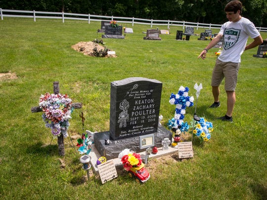 Ethan Poulter looks over the grave marker for Keaton