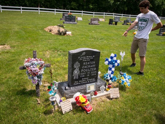 Ethan Poulter looks over the grave marker for Keaton Poulter at T'lam Cemetery by Red Rock Lake near Pella, Iowa, Saturday, June 14, 2018.