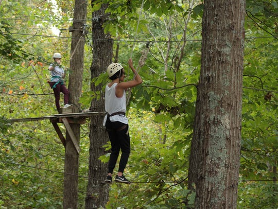 Two high school students participate in the high ropes