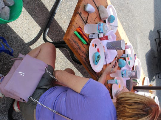Cancer Survivor event attendee paints rocks for the