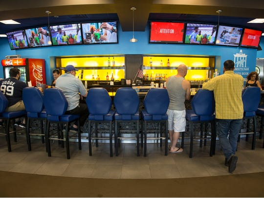 Patrons place bets at the Monmouth Park Sports Book by William Hill which recently opened to take wagers on all types of sporting events. 
