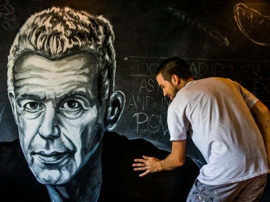Local artist Marcus Zotter works on a mural of Anthony Bourdain at 7th Avenue Social in downtown Naples on Wednesday, June 20, 2018. The mural will be a memorial to the late food icon who died last week.