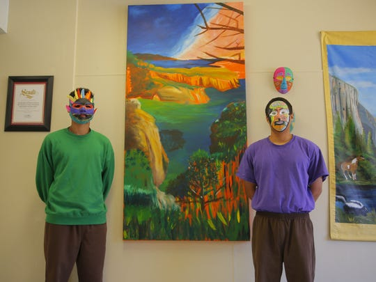 Michelangelo (left) and Devondre (right) showcase the painting they have both been working on while wearing handmade masks.