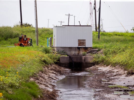 Water is pumped from the areas around Aransas Pass' berm on Monday, June 25, 2018. The levee can't be certified, which could lead to higher flood insurance rates.