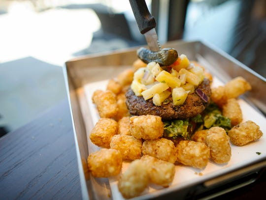 An open faced beef burger with a side of tots at Frenchie