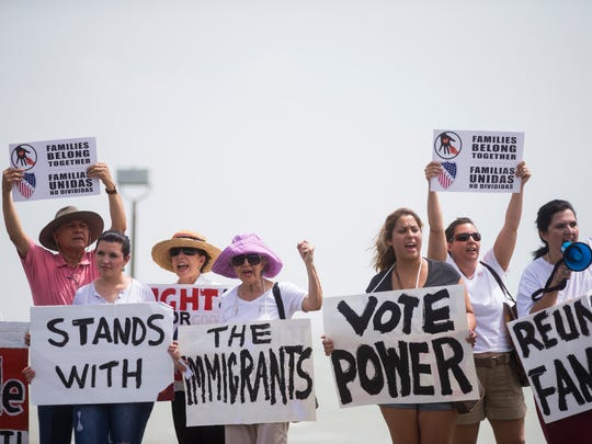 People hold up signs and protest during the Keep Families Together Rally in Cole Park on Saturday, June 30, 2018, in Corpus Christi, Texas.