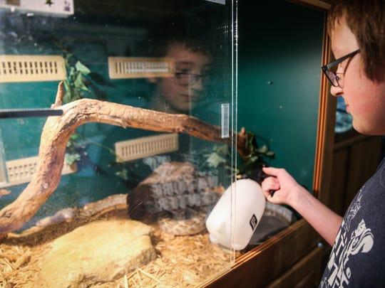 Phillip Bordner, 14, mists a cage for a snake Thursday,