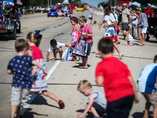 Kids rush to pick up candy during the Fourth of July parade Wednesday in Wall.