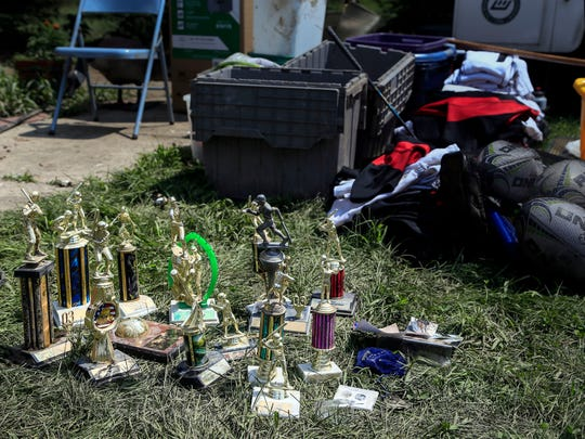 Trophies and sporting goods lay on the lawn of Nora