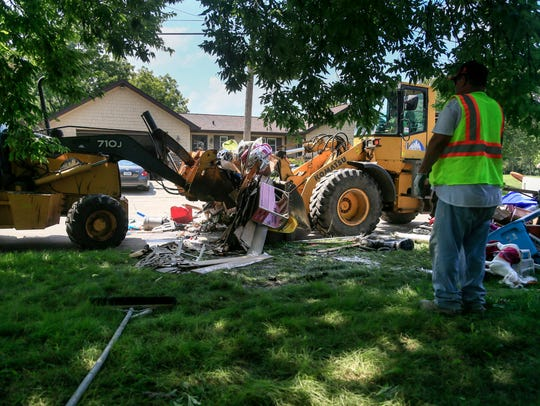 City workers load destroyed belongings from flood-damaged homes on East 35th Street in Des Moines on Tuesday, July 3, 2018.  