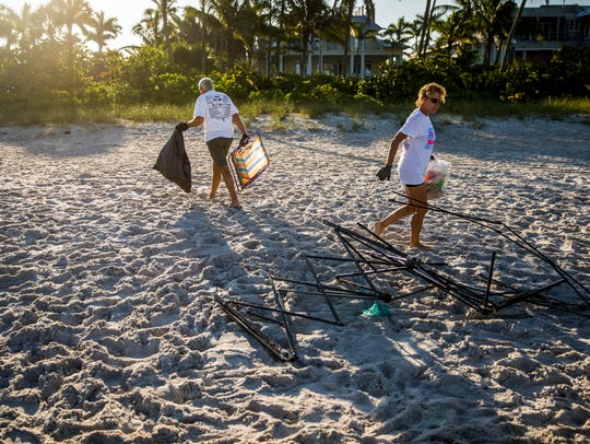Volunteers Amy Manley and Yancey Brame of Naples clean up trash left after the fireworks show the previous evening on the beach near Naples Pier on Thursday, July 5, 2018. The Old Naples Surf Shop organized the effort, which was sponsored by Keep Collier Beautiful, Full Spectrum Surf Company, and Surf Naples.