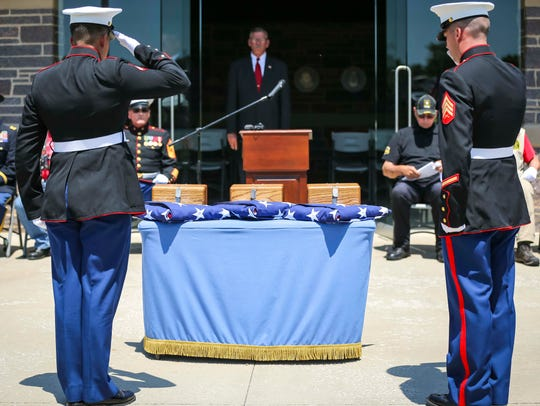 An Honor Guard salutes the remains of three veterans