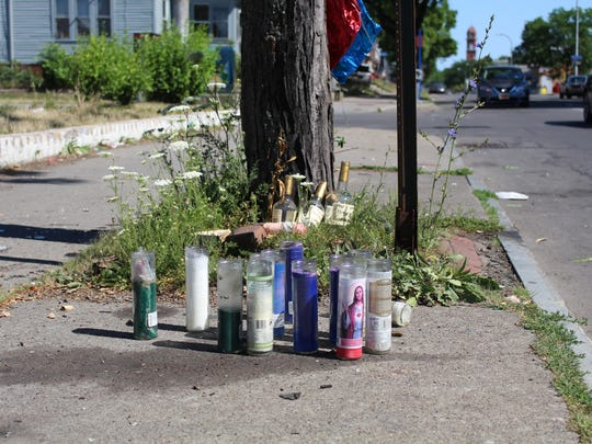 A display of candles at the site a 23-year-old man was shot on Hudson Avenue on Saturday night.