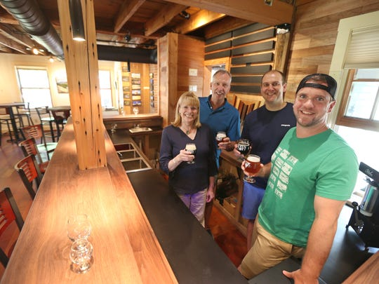 Property owners Karen and Paul Zachman, left, join brewery co-owners Seth Clark, second from right, and Casey Dunlavey, right, at the new Seven Story Brewing in Perinton Wednesday, July 11, 2018.  The brewery is set to open in August.