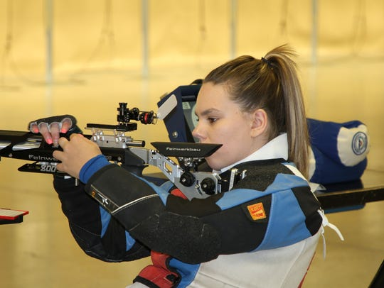 Castalia's Taylor Farmer prepares her rifle between