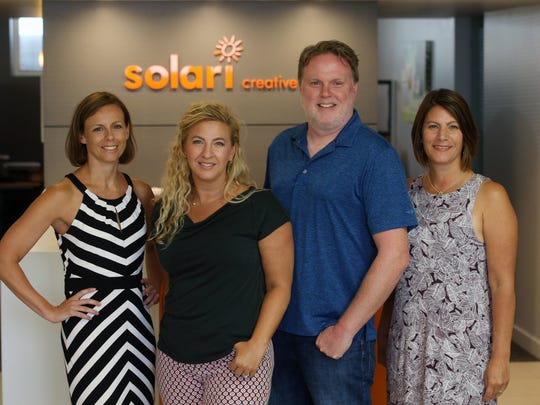 Jeanine Swierkocki, owner and creative director, Christine Ryan, president and art director, Michael Burke, vice president, and Debbie Byrne, business manager, pose together at Solari Creative, a Red Bank-based graphic design studio that's currently celebrating its 20th year in business, at their offices in Red Bank, NJ Friday July 13, 2018.