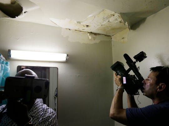 Reporters inspect peeling paint and mold in the bathroom