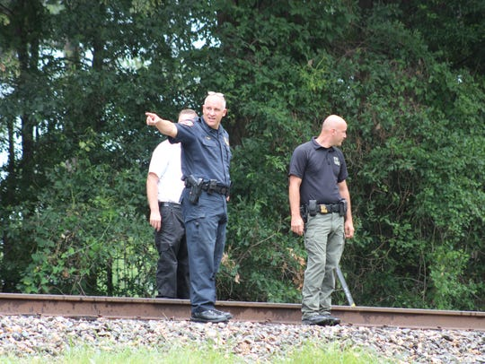 Investigators from the Louisiana State Fire Marshal's Office and Natchitoches Fire Department walk railroads tracks on July 18 where 6-month-old Levi Cole Ellerbe was found the night before. The baby was in critical condition after suffering burns from the fire. He later died at a Shreveport hospital.
