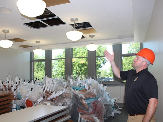 Pittsford Recreation Director Jessie Hollenbeck demonstrates light fixtures designed to capture the spirit of the building's history.