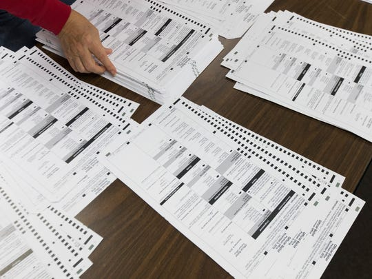 Workers sort absentee ballots as part of a recount