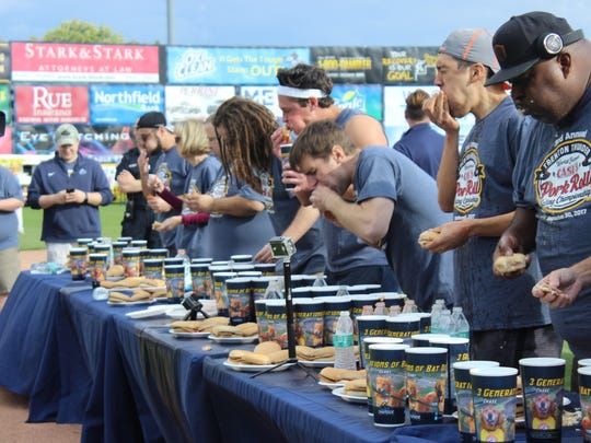 Competitors downing pork rolls at the Trenton Thunder World Famous Case's Pork Roll Eating Championship in Sept., 2017, with winner Carmen Cincotti in the middle