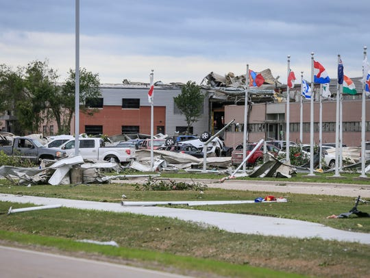Cars and debris are scattered around the Vermeer Global Pavilion Friday, July 20, 2018 after a tornado passed through Pella the day before.