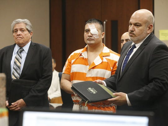 Hisaias Justo Lopez stands Tuesday with his lawyers,