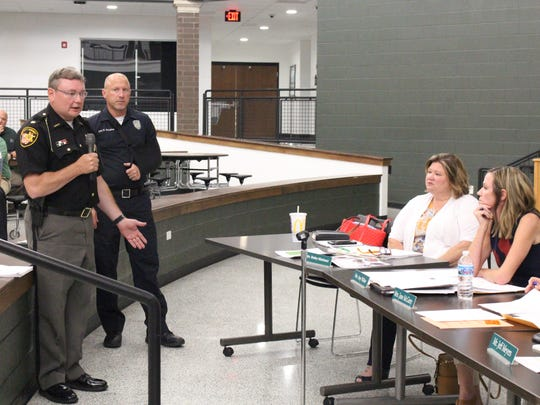 Richland County Sheriff's Office Major Joe Masi, left, talks with the Madison school board about a school resource officer Wednesday, July 25, 2018. Shelby school resource officer Keith Swisher stands behind Masi.