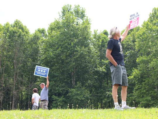 "(From left to right) Loudonville son and father Max Rhees and Ryan Rhees and West Salem resident Jimmy Hall hold signs during a rally in Loudonville on Sunday, July 29, 2018. The Rhees' sign says, ""We support natural gas and oil development,"" and Hall's sign says, ""Oil and water do not mix."""