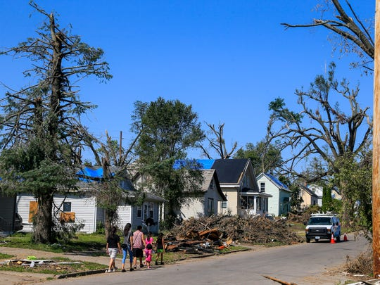 Marshalltown residents walk along Bromley St. Tuesday, July 31, 2018. The neighborhood was rocked by an EF-3 tornado that struck on July 19.
