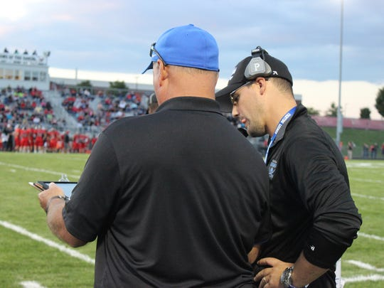Lee High head football coach Scott Girolmo, right, consults with his dad, Steve Girolmo, during a win over East Rockingham last season.
