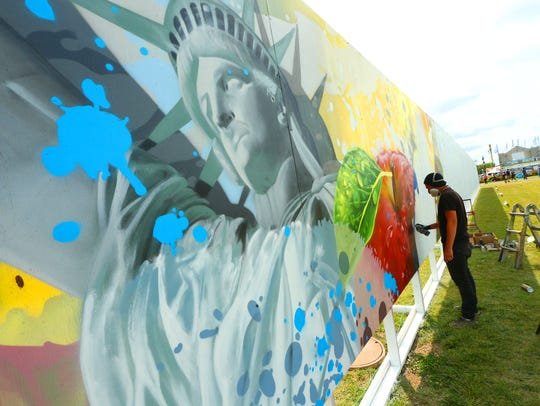 """Artist Ryan """"Arcy"""" Christenson works on his large mural"""